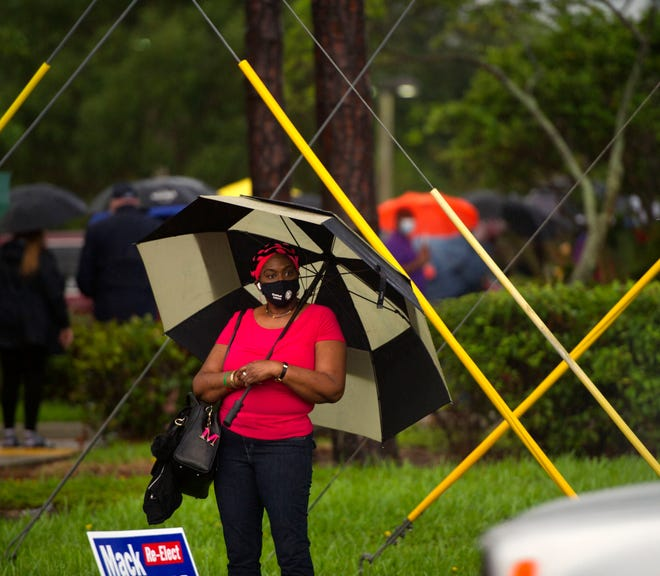 A woman lines up to vote Monday at the Lantana Road branch of the Palm Beach County library  during the first day of in-person early voting.