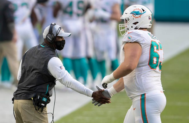 Dolphins coach Brian Flores encourages guard Michael Deiter during Sunday's victory over the Jets.