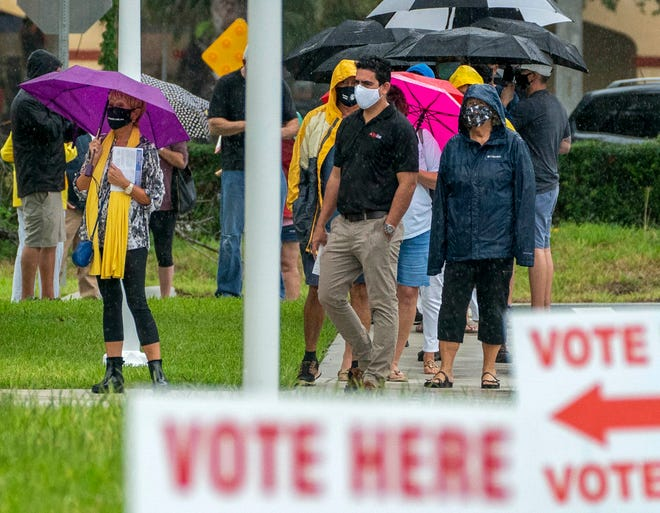 Voters line up in the rain to cast ballots Monday at the Jupiter Community Center on the first day of in-person early voting.