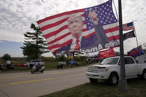 A flag waves in the wind before the arrival of President Donald Trump at an airport rally, October 14 in Des Moines, Iowa. (AP Photo/Charlie Neibergall)