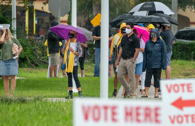 Voters wait in line to cast their ballots on the first day of in-person early voting at the Jupiter Community Center in Jupiter on Monday. [GREG LOVETT / THE PALM BEACH POST]