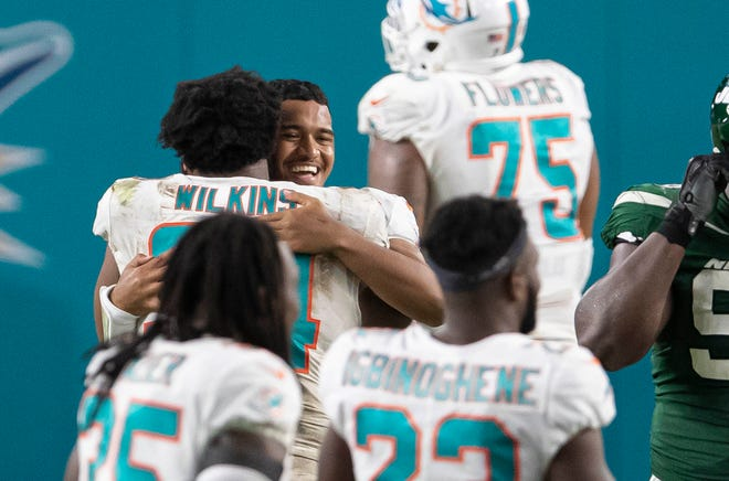Dolphins defensive tackle Christian Wilkins hugs Dolphins rookie quarterback Tua Tagovailoa after Sunday's 24-0 win over the Jets. Tagovailoa made his NFL debut late in the fourth quarter.