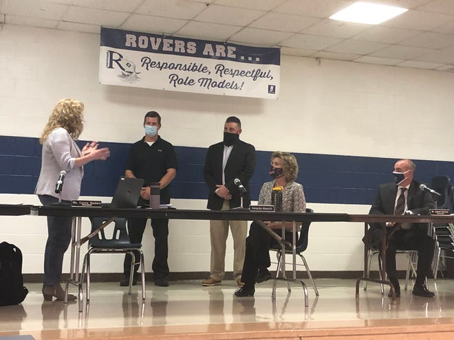 Rootstown Treasurer Connie Baldwin swears in new school board members Craig Mullaly and Paul McEwuen.