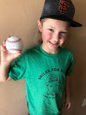 Miles Isbell holds a baseball signed by San Francisco catcher Buster Posey.
