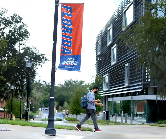 A student walks past a sign at the University of Florida as the first day of classes begin at the school, in Gainesville Fla. Aug. 31, 2020. Amid the Covid-19 pandemic, like colleges around the country, UF's freshmen application rate is so far down.   [Brad McClenny/The Gainesville Sun]