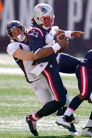 Denver Broncos linebacker Anthony Chickillo, left, sacks New England Patriots quarterback Cam Newton in the first half of an NFL football game, Sunday, Oct. 18, 2020, in Foxborough, Mass. (AP Photo/Charles Krupa)