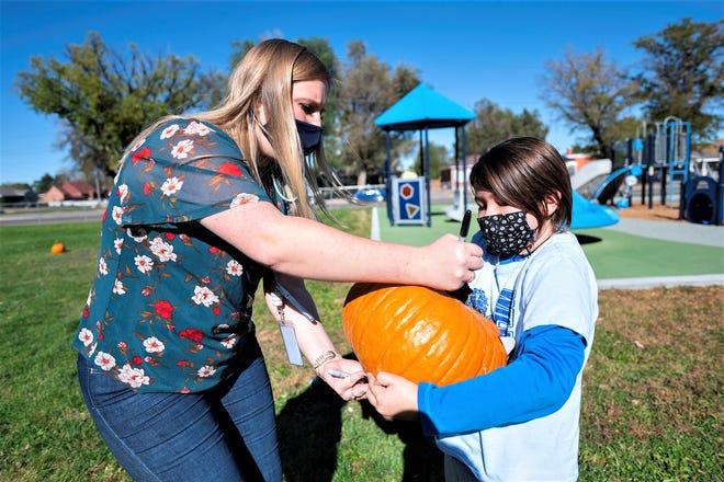 Carlile Elementary School fourth grade teacher Mellissa Libbert, left, writes Salvador Pollock's name on his pumpkin.