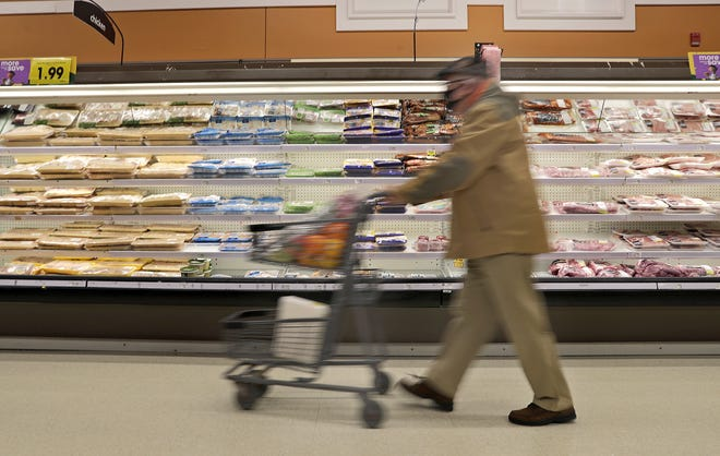 A shopper passes a well-stocked meat case in the Ballard Road Pick 'n Save in Appleton.