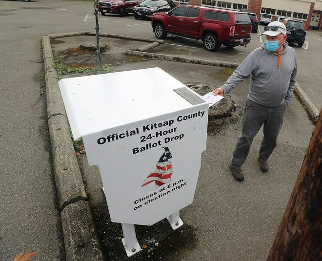 FILE — Chris Taylor, of Seabeck, places his ballot into the box at the Jenne-Wright Administration Center in Silverdale in October 2020.