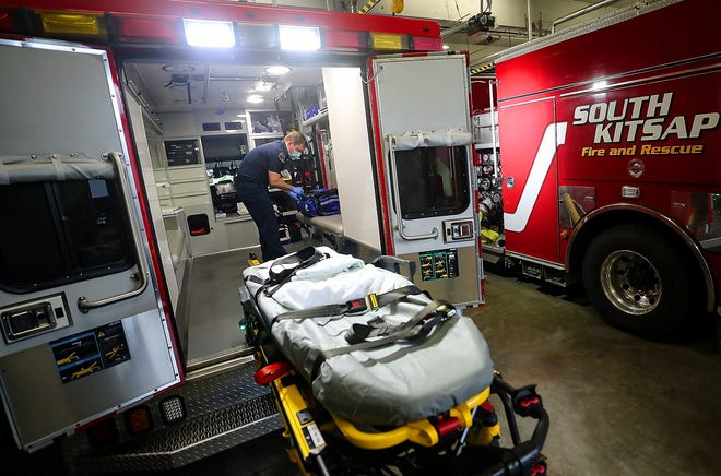 South Kitsap Fire and Rescue firefighter/paramedic Stephen Gutschow checks the equipment and supplies in the back of Medic 8 while in the apparatus bay of Station 8 in Port Orchard on Monday.