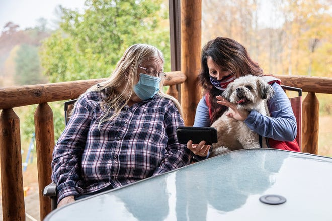 Billie Baxter Dubois, right, waves at her father William Baxter as she and his wife Rita Baxter Facetime with him on the phone on their porch Monday, Oct. 19, 2020. Baxter has been at the Chillicothe V.A. since August and has not had a personal visitation with his family since the start of the coronavirus pandemic.