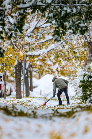 A Great Falls resident shovels snow in the downtown area Oct. 19. The city is off to its snowiest season on record but time will tell if the moisture continues to recharge parched soils that have the region in a moderate drought.