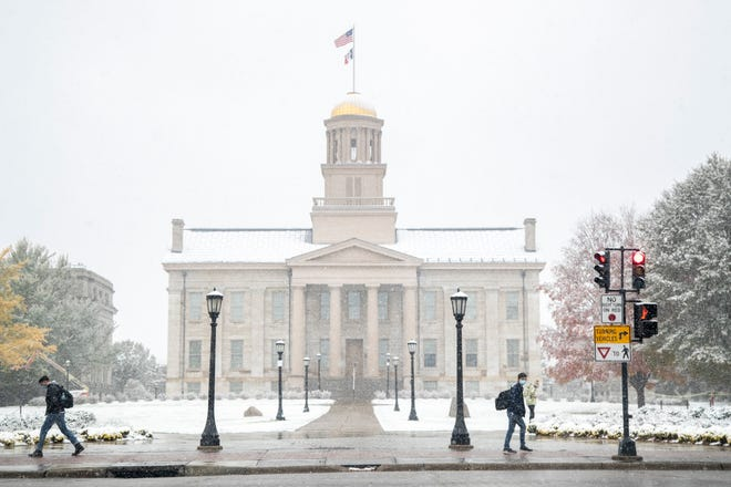 Students wearing face masks walk past the Old Capitol Building along Clinton Street as snow falls amid the novel coronavirus pandemic, Monday, Oct. 19, 2020, on the University of Iowa campus in Iowa City, Iowa.