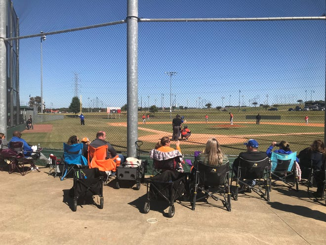 Parents watch their sons play baseball while listening to the college football game between Tennessee and Kentucky Saturday morning at the Sportsplex.