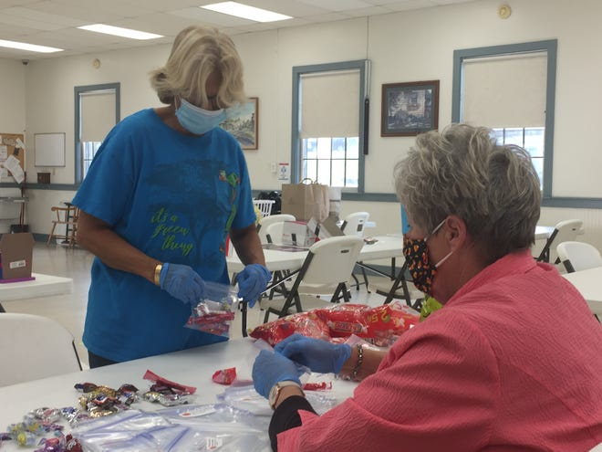 Brenda Wilson (standing) and Cathy McGlone prepare treat bags recently for the upcoming Halloween Walk in Lexington on Oct. 31.