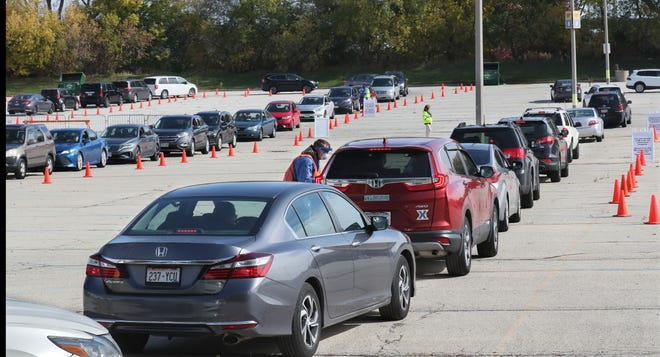 Cars snake through the parking lot on the way to the testing tent at the area's newest COVID-19 testing location at Miller Park on Monday. The site is staffed by the Wisconsin National Guard, Health Department and Milwaukee County EMS team.