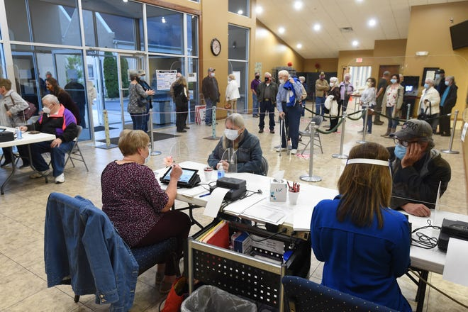 Voters check in to cast their ballots Monday moring at the First United Methodist Church in Mountain Home. Early voting for the Nov. 3 election opened Monday and continues through Tuesday, Nov. 2.