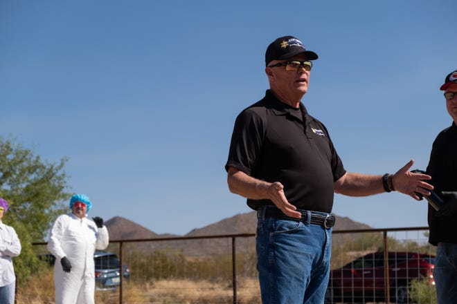 Jerry Sheridan speaks to the crowd before volunteers are sprayed with skunk water at his Fort McDowell home on Oct. 18, 2020.