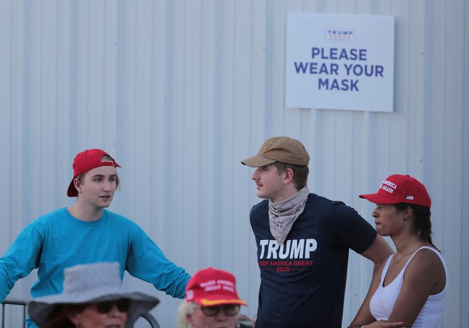 """A sign reminds people to wear masks as supporters of President Donald Trump wait for a """"Make America Great Again"""" rally to begin in Tucson on Oct.19, 2020."""