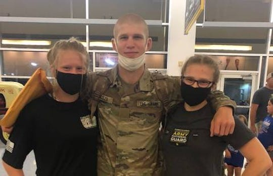 Tommy Dressler poses with his sisters, Abby (left) and Ashley (right) at Harrisburg International Airport after returning home from basic training.