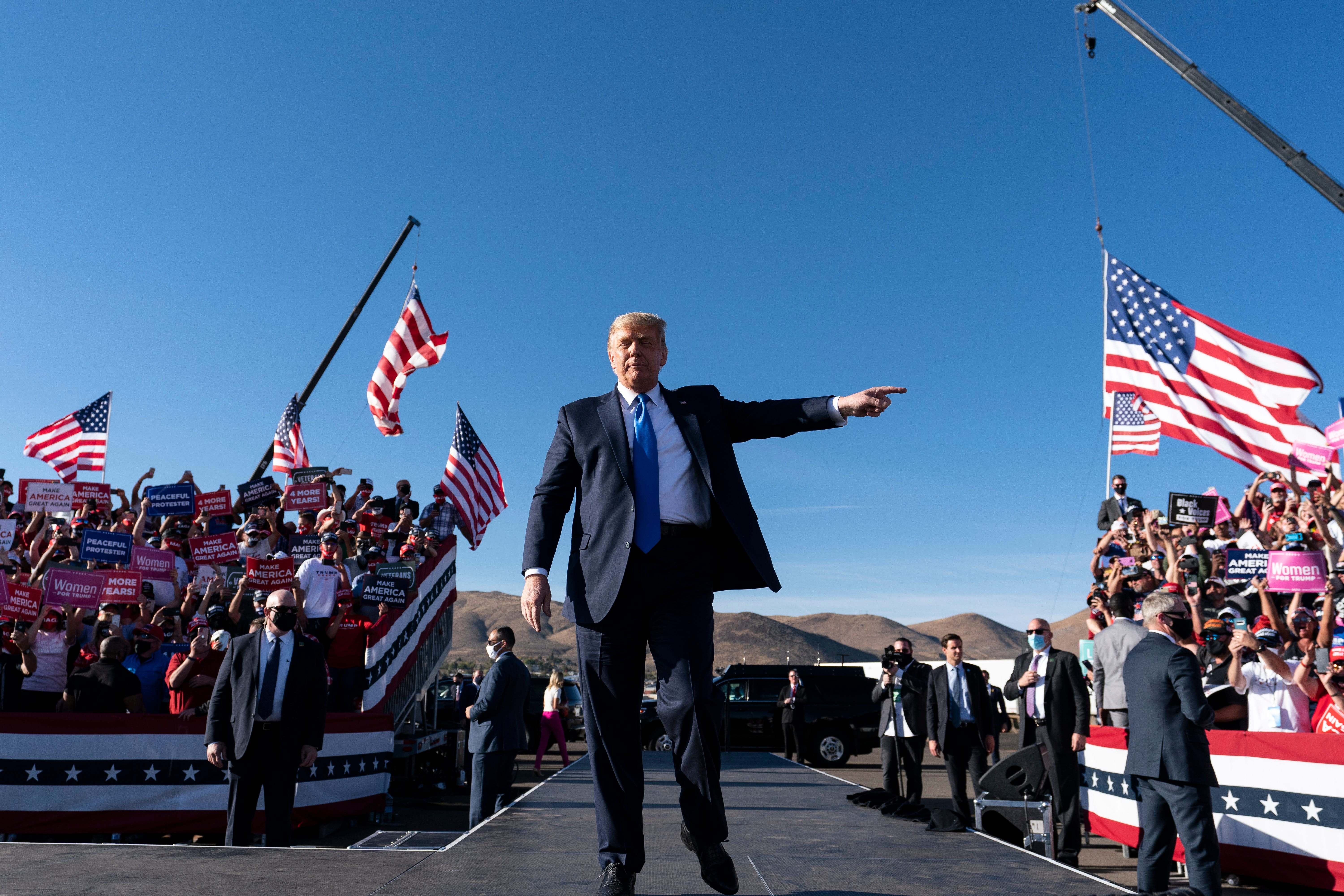 President Donald Trump points to supporters as he arrives to speak at a campaign rally at Carson City Airport, Sunday, Oct. 18, 2020, in Carson City, Nev.