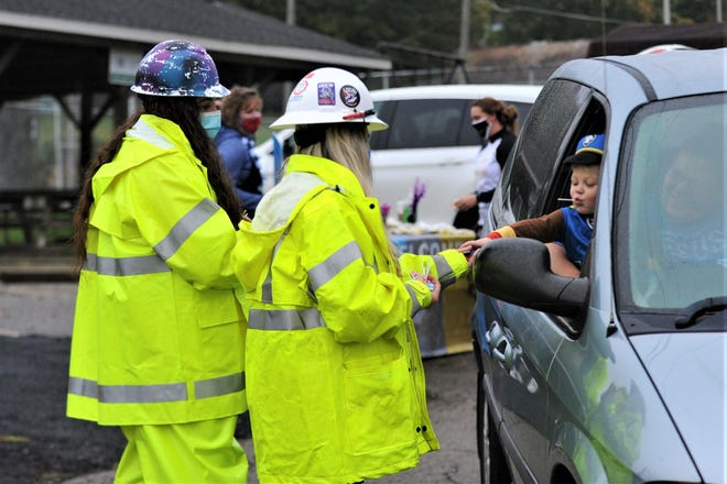 Shannon Walters (left) and Stephanie Hinds (right) with Muskingum Behavioral Health hand out candy to a child dressed as Chase from Paw Patrol on Monday as Eastside Community Ministry held its Drive Thru Trick or Treat.