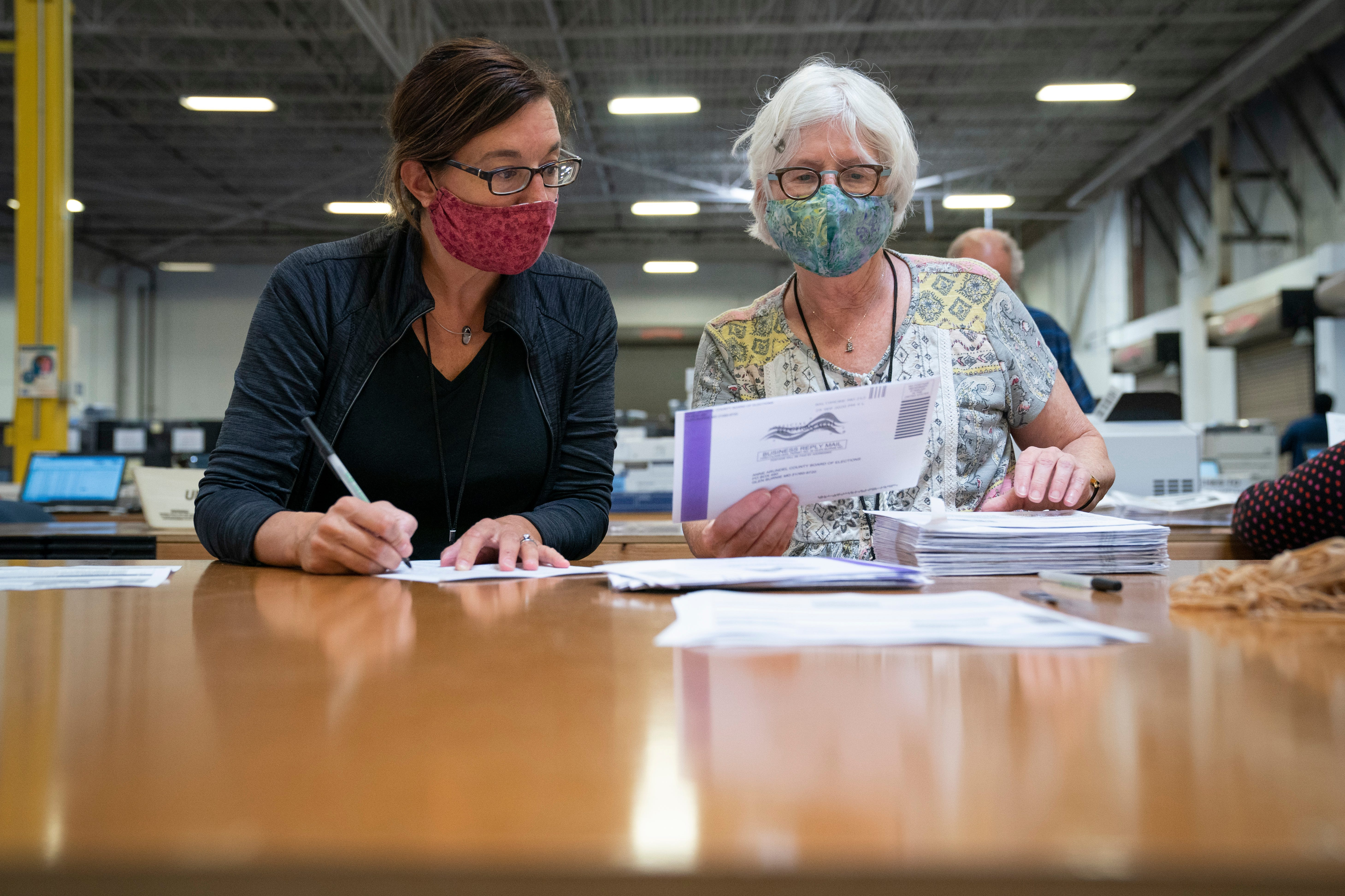 Working in bipartisan pairs, canvassers process mail-in ballots Oct. 7, 2020, in a warehouse at the Anne Arundel County Board of Elections headquarters in Glen Burnie, Md.