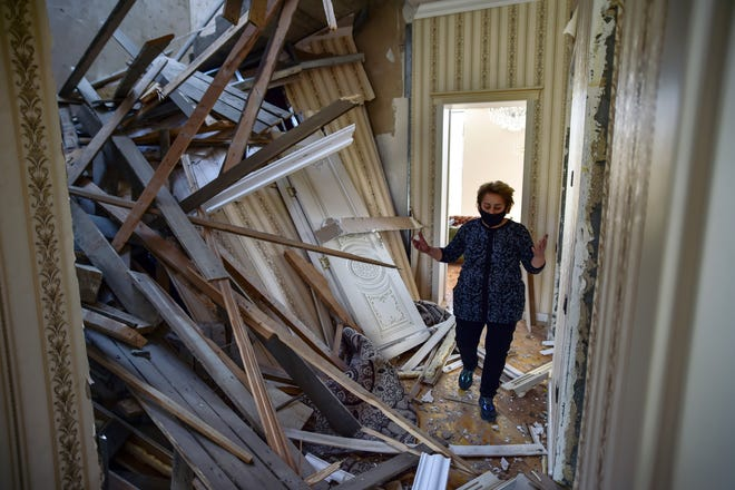 An Azerbaijani Turkish woman looks at the her damaged house in Ganja, Azerbaijan's second largest city, near the border with Armenia, after rocket fire overnight by Armenian forces for second time in a week, early Saturday, Oct. 17, 2020.