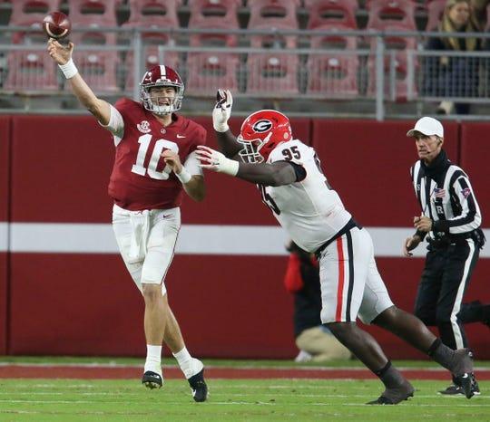 Alabama quarterback Mac Jones throws under pressure from Georgia defensive lineman Devonte White during the second half at Bryant-Denny Stadium.