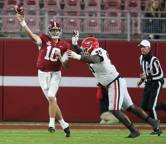 Alabama quarterback Mac Jones throws under pressure from Georgia defensive lineman Devonte White during the teams' game earlier in the season. Jones, a Heisman Trophy finalist, leads the nation in efficiency rating and completion percentage.