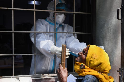 A health worker collects a swab sample from a resident to test for the COVID-19 coronavirus at a testing centre in New Delhi on Oct. 19, 2020.