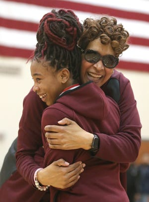 Kenmore-Garfield girls basketball coach Yontami Jones hugs I'anna Lopp after defeating Buchtel in the City Series Championship game in 2019.