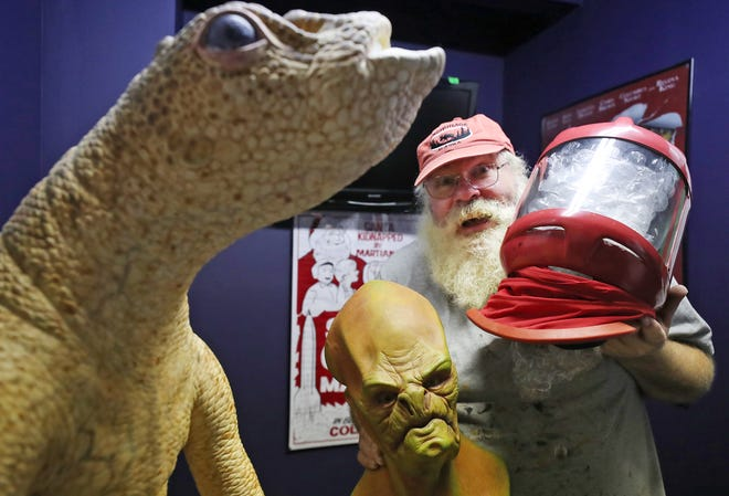 """Mark Klaus, owner of Alien Vacation Mini Golf, holds an alien head and Data's invisibility helmet from the movie """"Star Trek: Insurection"""" under the watchful gaze of a worm guy from the """"Men in Black"""" movies on Oct. 15 in Medina."""