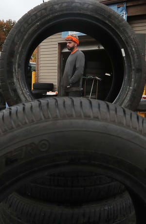 Samir Abdul, owner of West Side Tire, stands behind a stack of display tires in front of his Akron business Tuesday.