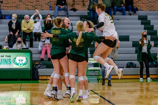 Rock Bridge's Cassie Gray (5) jumps in with her teammates after the Bruins completed a sweep against Helias during a Central Missouri Activities Conference match Monday night at Rock Bridge High School.