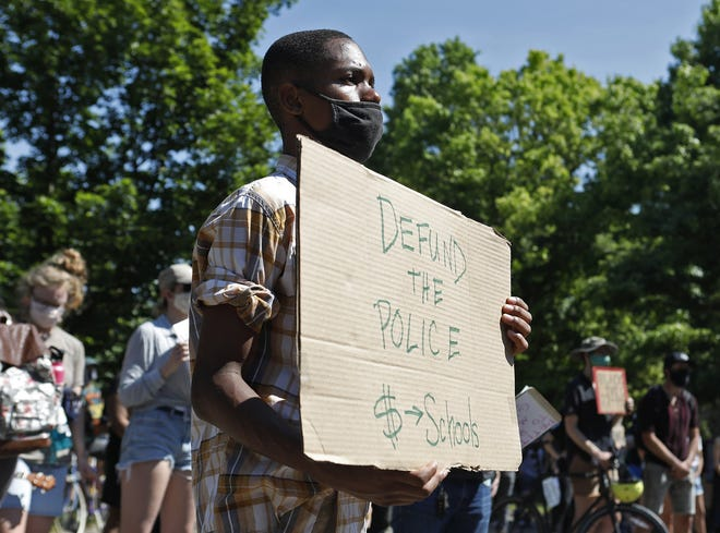 In this file photo, Denzel Warren, 18, holds a sign at a protest at Mayor Andrew Ginther's home in Columbus on June 20. The BQIC (Black Queer Intersectional Collective) was calling for the defunding of Columbus police and to bring attention to racial equality issues.