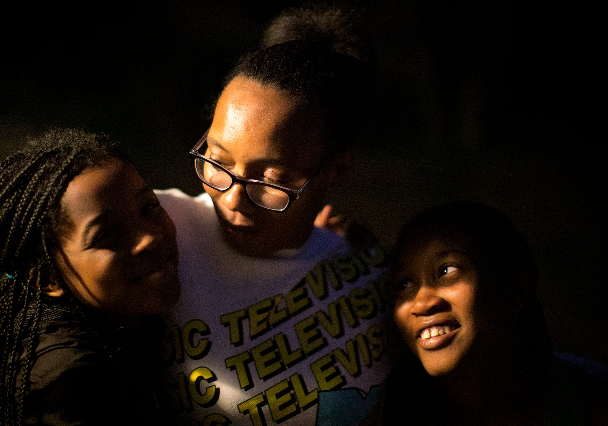 Armani Wells, 13, right and Arihanna Wells, 8, left, hug their mother, Cherise Harris, on their back porch in Painesville, Ohio, in October 2020. The family house is a block from a city-owned power plant, built in the 1800s, that still burns coal.