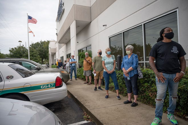 People line up around 9:30 a.m. waiting for the doors to open at 10 a.m. for early voting at the Supervisor of Elections Office in Tavares on Tuesday. [Cindy Peterson/Correspondent]