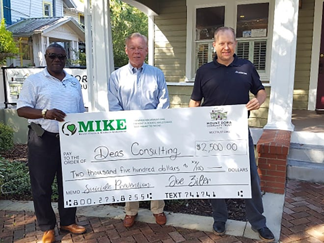 Isaac Deas of Deas Consulting, Rob English, Executive Director of the Mount Dora Community Trust and Joe Ziler of Kevco Builders stand in front of the Mount Dora Community Trust with the first donation to help fund counceling for people who can't afford it.