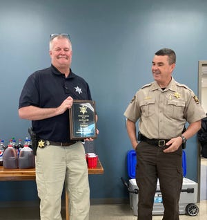 Dewayne Miller (left) stands with Sheriff Richie Simmons (right) holding a plaque to celebrate his years of service to the Sheriff's Office.