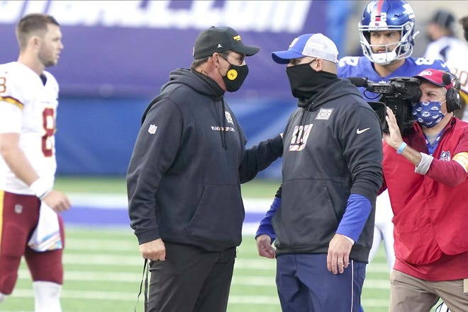 Washington Football Team coach Ron Rivera (left) talks to the New York Giants' Joe Judge after Sunday's game in East Rutherford, New Jersey. The Giants won 20-19.