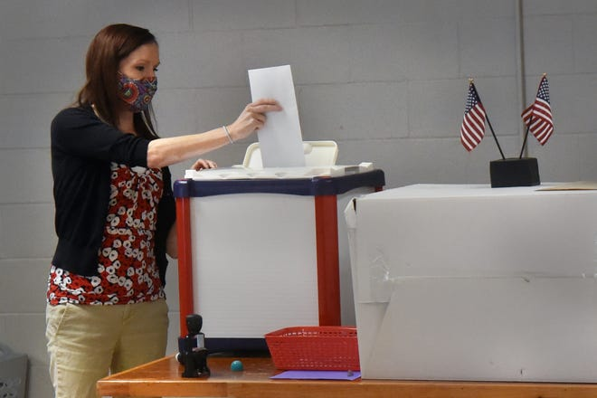 Rochester Deputy City Clerk Cassie Givara puts a ballot within an envelope in the secured box after officially stamping the outside after getting it from an early voting resident at the polling site held in the Community Center Monday.