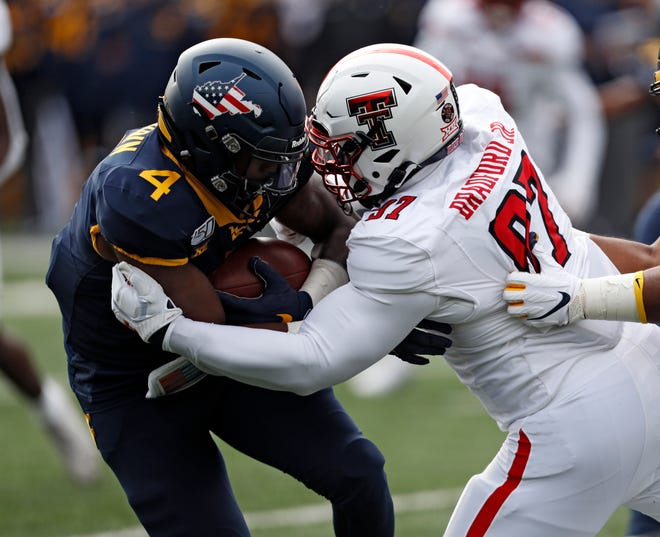 Texas Tech defensive lineman Tony Bradford (97) hits West Virginia running back Leddie Brown (4) during the Red Raiders' 38-17 victory last year. Tech held Brown to a team-high 16 yards rushing that day, but Brown is the FBS' fifth-leading rusher with 515 yards going into this week's game.