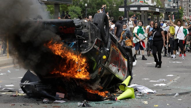 Protesters demonstrate in May as a Salt Lake City police vehicle burns in Salt Lake City. Investigators studied video footage to find Jackson Stuart Tamowski Patton, 26, who is accused of tossing a combustible substance into the patrol car, feeding the flames that destroyed it, prosecutors said in court documents.