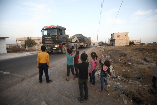 A Turkish military convoy drives through the village of Urum al-Jawz, in Idlib province, Syria, on Tuesday. Turkish troops in northwestern Syria have been evacuating one of their largest military bases in the area, which was surrounded by Syrian government troops for months, activists said Tuesday. There was no immediate comment from Turkish officials.