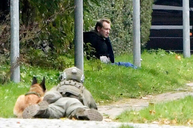 A police office watches Peter Madsen as he sits on the side of a road after being apprehended following a failed escape attempt in Albertslund, Denmark, on Tuesday. The self-taught Danish engineer, who was convicted of torturing and murdering a Swedish journalist on his homemade submarine in 2017 before dismembering her body and dumping it at sea, on Tuesday was captured after attempted prison escape outside the suburban Copenhagen jail where he is serving life-time sentence.