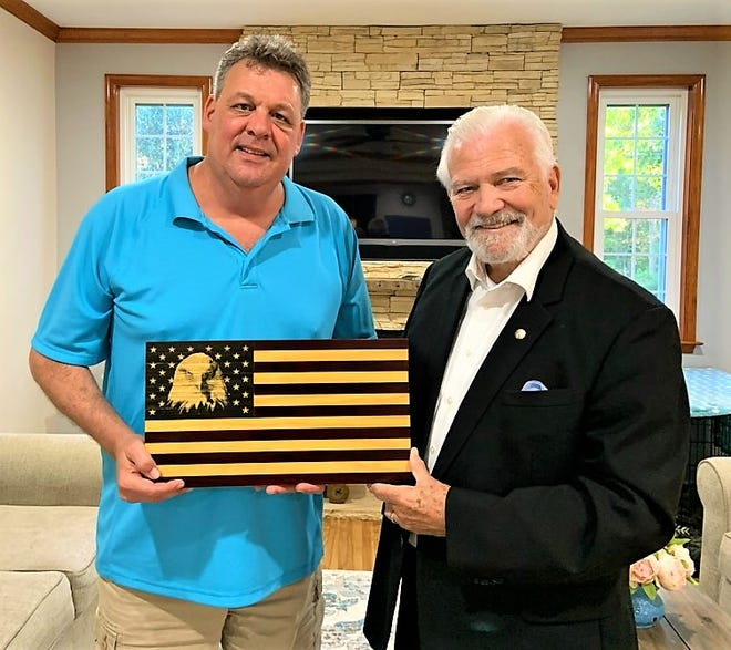 Richard Harpster, left, presents one of his special hand-crafted flags to Dave Skocik for an auction that will benefit the Veterans Watchmaker Initiative in Odessa, as it plans for a larger facility in Middletown. VWI trains disabled veterans to become certified watchmakers into a lucrative specialization in demand across the nation.