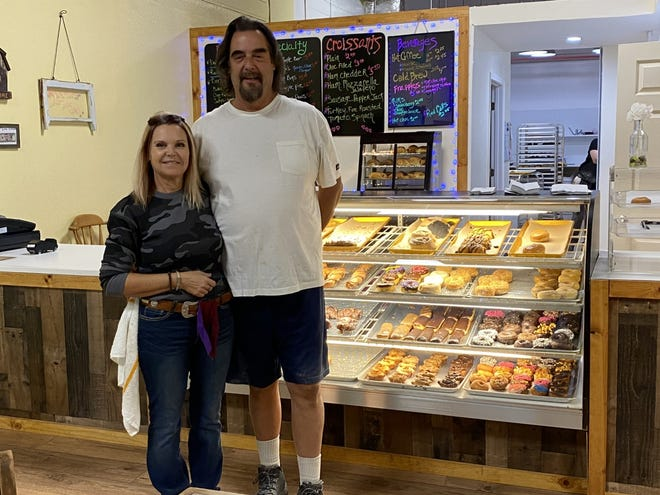 Denise and Jeff Fields, owners of Papa's Donuts in Mount Shasta, stand beside their fully stocked case of goodies Tuesday morning, Oct. 20, 2020.