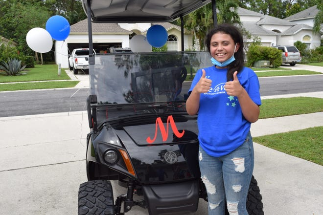 Marianna Mohar, 12, of Wellington poses with the customized golf cart she received from Make-A-Wish Southern Florida.