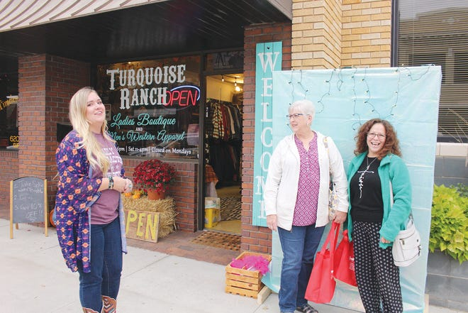 Turquoise Ranch employee Laura Schwab (left) visits with Ladies Night Out shoppers Jean Tharp, Pratt (middle) and Lorie Thackeray, Mesa, Ariz. (right) October 15 in Prattas they take a photo for discount in the store. More than 18 stores were open late for the annual shopping event last week.
